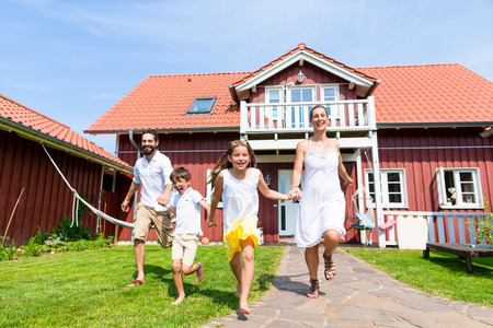 house family: Happy family running on meadow in front of house on front yard grass Stock Photo