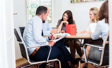 law: Lawyers in law firm reading documents and agreements at large conference table Stock Photo