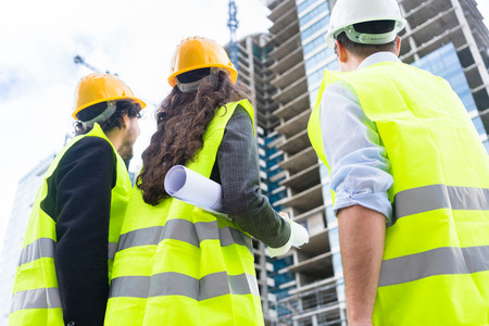 highriser: Construction engineers or architects at building site of highrise building Stock Photo