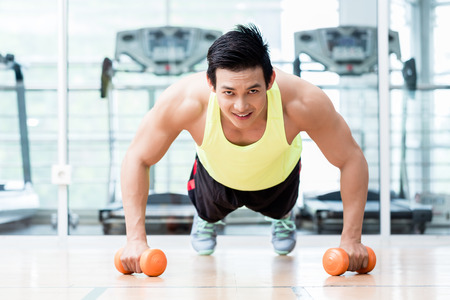 asian guy: Frontal view of male bodybuilder doing pushups while holding dumbbells in his hands