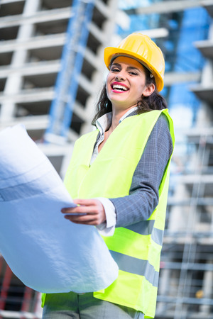Female architect studying drafts while visiting large construction site