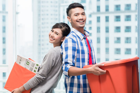 Young indonesian couple, woman and man, carrying moving boxes in their new skyscraper apartment