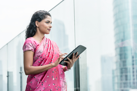 Confident business woman using a tablet PC while wearing traditional Indian clothing outdoors