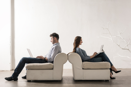 Man and woman sitting back-to-back in empty room working on laptops Stock Photo