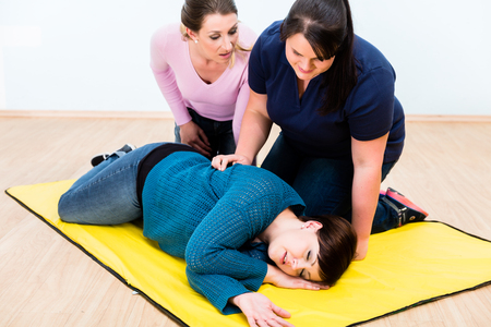 responses: Women in first aid class training to position injured person