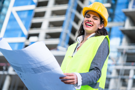 housing lot: Female architect studying drafts while visiting large construction site