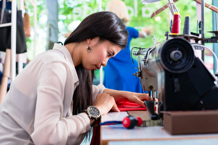 Asian tailor woman sewing dress with machine