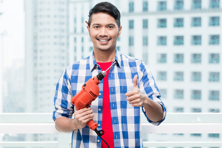 highriser: Young indonesian man with power drill, ready for home improvement Stock Photo
