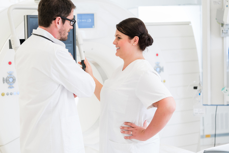 Doctor and nurse discussing image of MRI scan standing in front of the machine in hospital