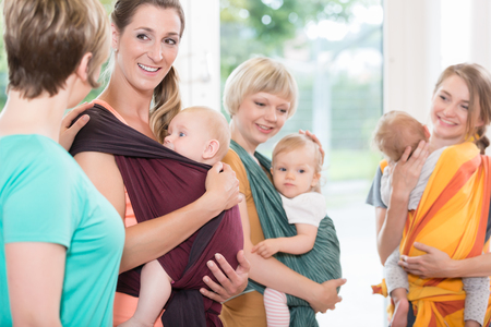 Group of women learning how to use baby slings for mother-child bonding Stockfoto