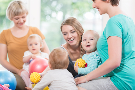 Young women in mother and child group playing with their baby kids Stock Photo