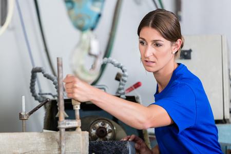 Female stonemason adjusting workpiece in polishing machine