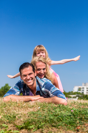 happy families: Parents and daughter in meadow, daughter spreading their arms like wings