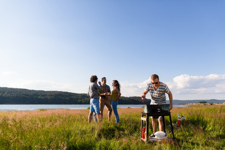griller: Gang of young men and women having barbecue at lake in summer