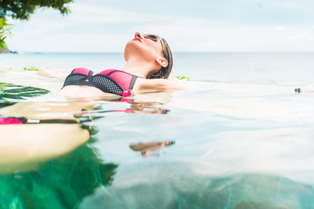 backstroke: Woman in summer vacation relaxing swimming in pool with the ocean in the background