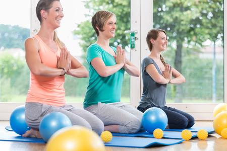 nacimiento: Las mujeres jóvenes haciendo yoga durante la lección de la recuperación posnatal