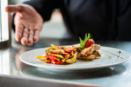 Chef zeigt stolz Nahrungsmittel oder Gericht er in Restaurantküche gekocht Standard-Bild - 71102931
