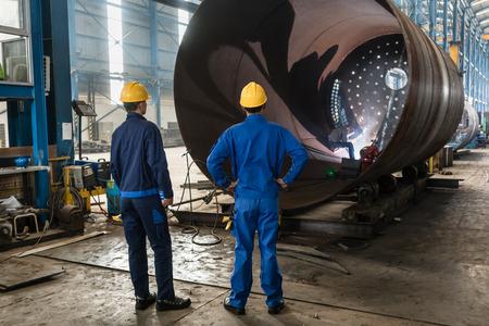 공장 내부에서 금속 실린더의 제조를 감독하는 2 명의 숙련 된 근로자 스톡 콘텐츠