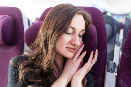 Woman traveler having a nap in airplane cabin travelling to her vacation Stock Photo