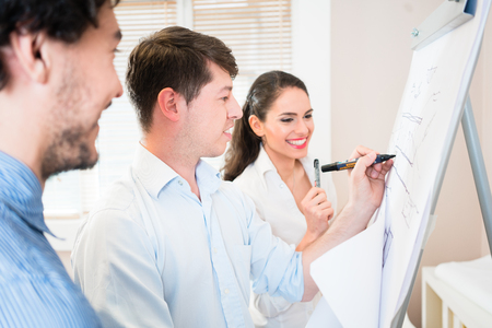 Architects and civil engineers talk about construction plans for building at flipchart Stock Photo