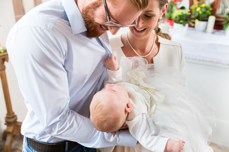 Young parents at the church with their baby wearing a christening gown  Stok Fotoğraf