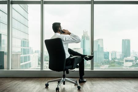 Retrovisione dell'uomo d'affari che parla sul telefono mentre sedendosi in un ufficio con la vista panoramica della città