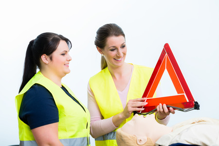 Women in first aid course learning to secure road crash site