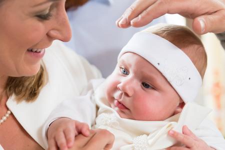Madre con su bebé en la ceremonia de bautizo, con el sacerdote sosteniendo su mano sobre la cabeza del bebé