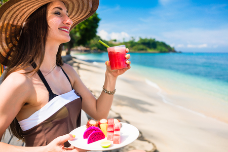 water wave: woman tourist at tropical beach eating fruit like water melon, pineapple and barbary fig for breakfast Stock Photo