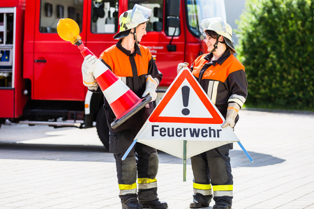 public spirit: Female fire fighters in emergency operation setting up attention sign Stock Photo