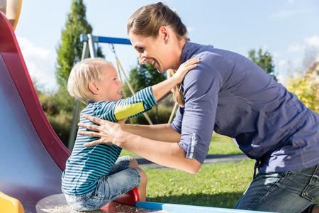 Woman and little boy chuting down slide at playground Standard-Bild
