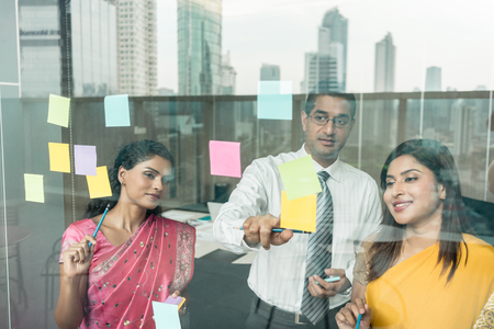 prioritization: Three Indian employees sticking reminders on glass wall with business tasks and deadlines in the office Stock Photo