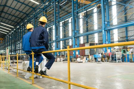 Rückansicht von zwei Arbeiter während des Bruches im Inneren einer Industriehalle Standard-Bild - 74014427