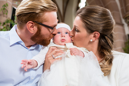 Young parents kiss their baby at the same time after the christening ceremony