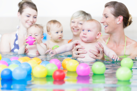 Moms and children at infant swimming lesson playing with balls