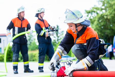 Fire fighter connecting hoses in front of fire engine Stock Photo - 74039868