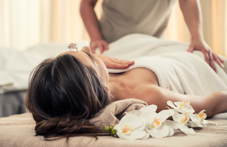 Young woman relaxing on massage bed under the positive therapeutic effect of a crystal placed on her forehead at luxury spa and wellness center Stock Photo