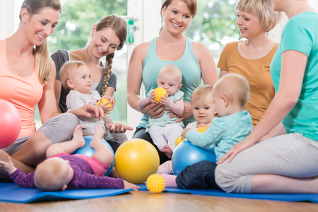 Young women in mother and child group playing with their baby kids Stock Photo - 75683332