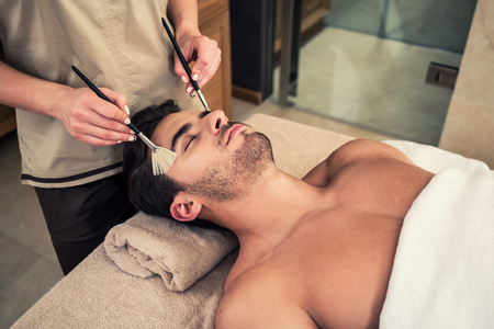 traditional: Close-up of young man lying down on massage bed during traditional Chinese facial treatment at Asian beauty center