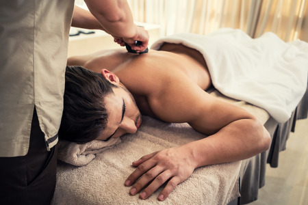 curative: Young man relaxing during traditional massage with hot stones at Asian spa and wellness center