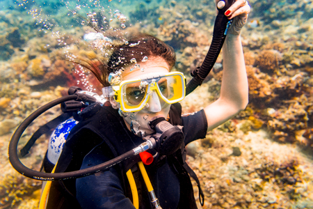 Woman in vacation scuba diving down to tropical coral reef