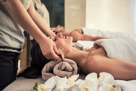 salon and spa: Relaxed woman lying down on massage bed during facial treatment at Asian spa and wellness center Stock Photo