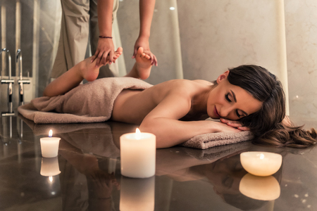 salon and spa: Young woman lying down while enjoying the stretching techniques of a professional Thai massage in luxury spa and wellness center Stock Photo