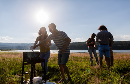 river: Young people making Barbecue at lakeside meadow, men and women