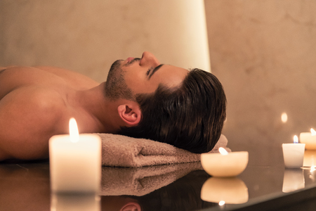 traditional: Young man relaxing on massage table surrounded by scented candles at Asian spa and wellness center Stock Photo