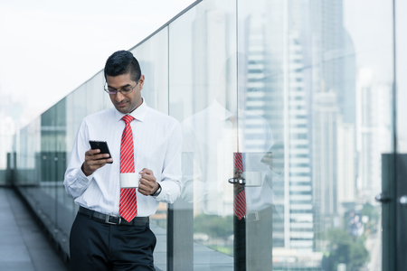 mobile: Indian businessman drinking coffee and using a smartphone on the terrace of a modern building