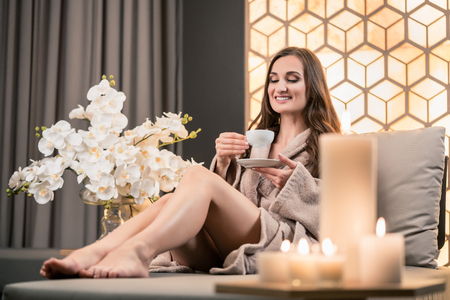 oriental bathrobe: Relaxed young woman drinking herbal tea while sitting on sofa before spa treatment in wellness center