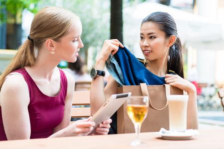 Dvě mladé ženy diskutují o nákupu oblečení, když sedí v restauračním stolu a objednávají jídlo, protože atraktivní asijské ženy ji vytahují z tašky. Reklamní fotografie