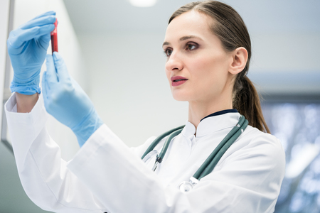 Doctor in medical laboratory looking at blood test she is holding in her hand