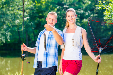 Fishing couple, man and woman, on lake being proud of their catch Stock Photo